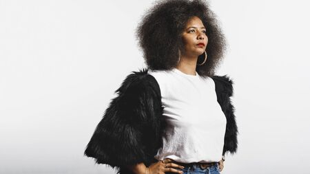 Woman in afro hairstyle standing against white background. Portrait of woman in fur coat looking away.