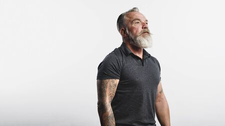 Senior man with tattoo on arms standing against white background. Portrait of old muscular male with a white beard looking away. 스톡 콘텐츠