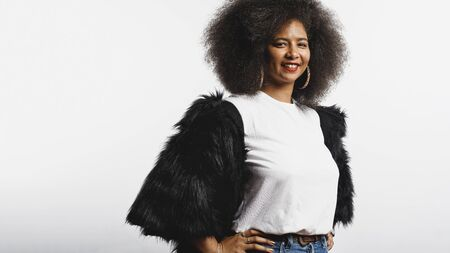 Smiling woman in afro hairstyle standing against white background. Portrait of cheerful woman in fur coat looking at camera. 스톡 콘텐츠