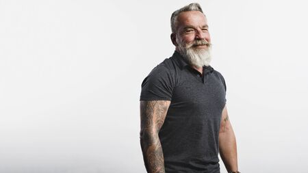 Portrait of old muscular male with white beard looking at camera. Smiling senior man with tattoo on arms standing against white background. 스톡 콘텐츠