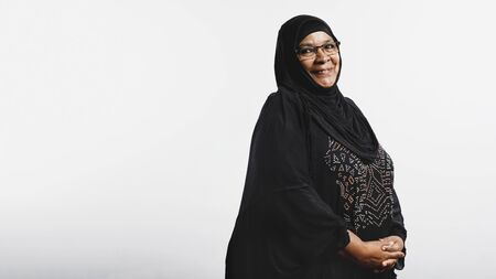 Senior muslim woman in hijab isolated on white background. Smiling arabic woman in eyeglasses and black hijab looking at camera.