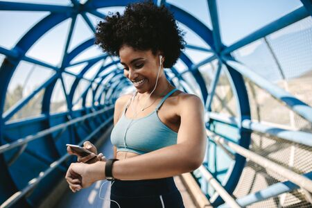 Fit female runner using smart watch and mobile phone to monitor her performance. Sportswoman feeling happy after workout progress.