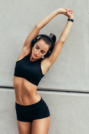 Fitness woman stretching in morning. Sporty woman doing warm up workout by a wall. 版權商用圖片