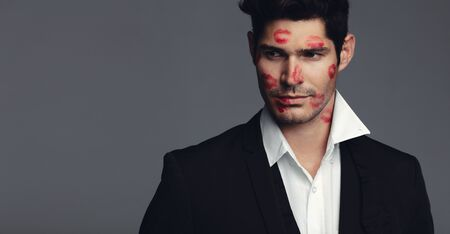 Handsome young man with lipstick marks of kisses on his face. Handsome male model in black blazer looking away while standing against grey background.