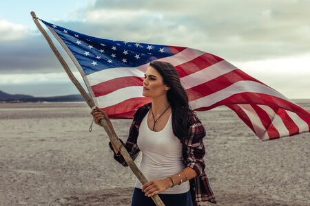 Beautiful caucasian woman holding an American Flag while standing on the sea shore. Young woman with the USA flag on beach.