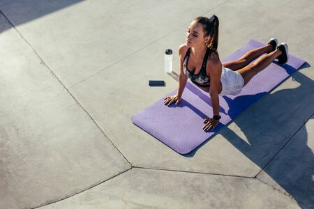 Sports woman practising yoga outdoors. Female in sportswear doing yoga stretches workout in morning.