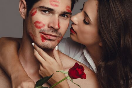 Close up of woman kissing her boyfriend. Man kissed by girlfriend with lipstick kiss marks on the face.