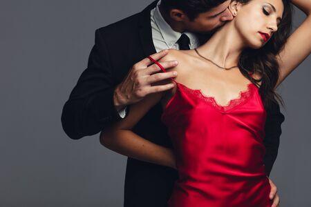 Coppia alla moda in un momento sensuale su sfondo grigio. Giovane uomo e donna colti in un momento romantico