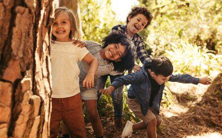 Süße lächelnde Kinder, die hinter dem Baum im Park hervorschauen. Gruppe von Kindern, die das Verstecken in einem Wald genießen.