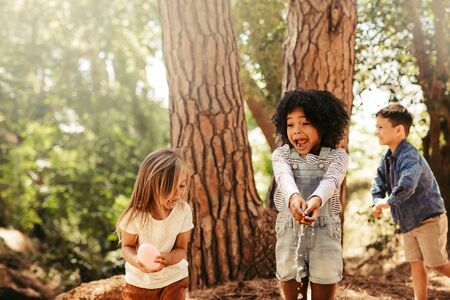 Girls bursting water balloons with hands in a park. Group of kids having fun in forest.