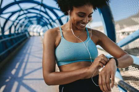 Fit female runner using smart watch to monitor her performance. African Woman setting fitness app on her smart watch before running session.