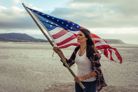 Attractive young woman holding an American Flag while standing on the beach. Young woman in casuals with the USA flag. Foto de archivo