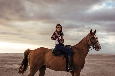 Portrait of young lady sitting on her horse and looking away. Female horse riding on beach in evening. Stok Fotoğraf