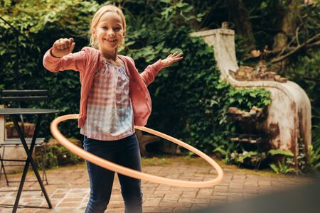 Smiling kid playing with a hoop in her backyard. Girl having fun turning a hoopla ring around her waist.