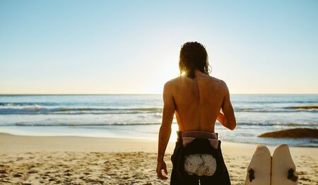 Rear view shot of young man standing on the beach with surf board. Male surfer relaxing on the sea shore on a summer day.