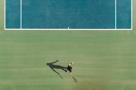 Aerial view of young male tennis player playing on hard court. Professional tennis player hitting a forehand on court.