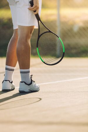 Cropped shot of sportsperson with racket on tennis court. Male tennis player a on hard court baseline.