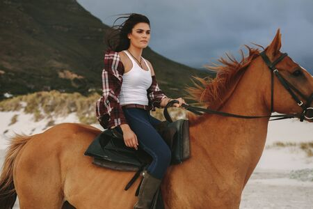 Attractive young woman riding a horse at the beach in evening. Cowgirl riding with her stallion on the sea shore.