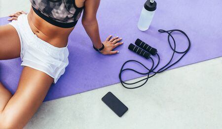 Cropped shot of a woman in fitness wear relaxing after workout sitting on a yoga mat with mobile phone, water bottle and skipping rope beside her.