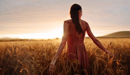Young woman hand feeling the top of a field of wheat crop in golden sunlight at sunset.