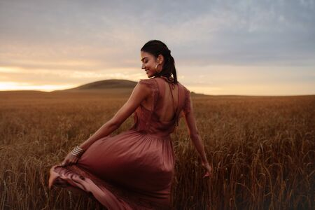 Young woman feeling happy in field of wheat crop at sunset. Female enjoying a day in nature. Foto de archivo