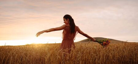 Young woman standing in wheat field holding bunch of flowers and enjoying during sunset time. Female with her arms outstretched standing in filed with flowers.