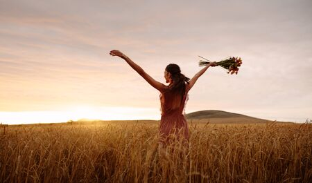 Happy woman holding bunch of flowers standing with her hands outstretched at a wheat field. Female enjoying in countryside during sunset.