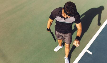 Top view of young man playing tennis bouncing the ball on the hard court for the serve. Tennis player about to serve the ball in a match.