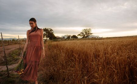 Young woman holding flowers in the wheat field. Girl strolling with bunch of flowers in an agricultural field during sunset. Banco de Imagens