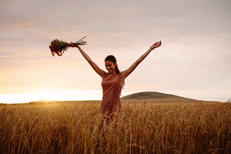 Happy woman with flowers walking in a wheat field. Female enjoying a day in field during sunset. Banco de Imagens