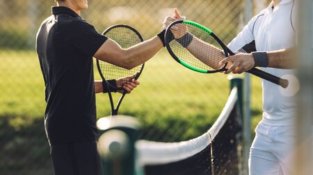 Two young man shaking hands after playing tennis. Tennis players shaking hands over the net after the match.