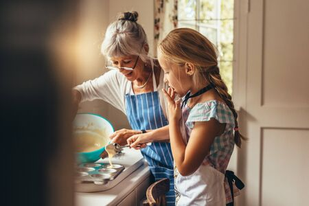Grandmother teaching kid to make cup cakes. Happy grandmother and kid pouring cake batter in cup cake moulds. 스톡 콘텐츠 - 139474882