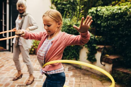 Girl playing with a hoopla ring in her backyard. Granny and kid practicing rotating a hula hoop around their waist. Reklamní fotografie