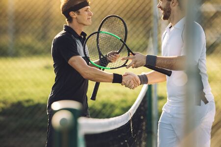 Professional tennis players shaking hands at the net. Two sportsmen shaking hands over the net after the match. Stock Photo