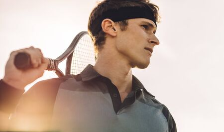 Close-up of a professional tennis player standing outside on a sunny day. Male tennis player with racket looking away.