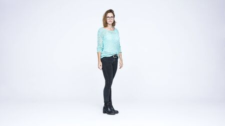 Woman in eyeglasses standing against white background. Businesswoman with short brown hair looking at camera.