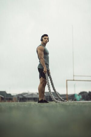 Man taking rest from battle rope workout. Muscular man doing fitness workout while it rains with battle ropes on a field.