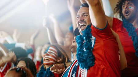 Excited USA football fans and supporters celebrating a goal being scored in the sports stadium. American soccer fans cheering their team in the stands.