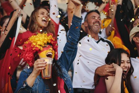 Supporters in the stadium during a match cheering their team. Deutsch supporter at the soccer stadium with confetti falling. Banque d'images