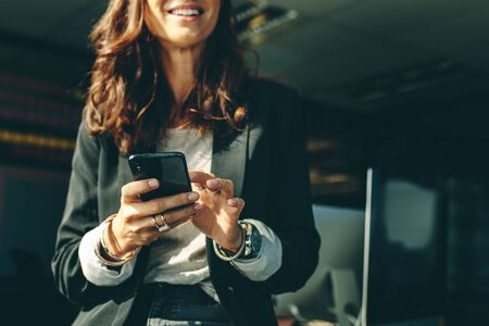 Cropped shot of a businesswoman with a on mobile phone in office. Business executive using a phone in office. Imagens