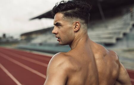 Rear view of healthy young man standing on track field. Muscular man taking a break from workout at a stadium.