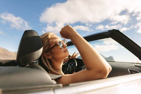 Attractive woman with sunglasses traveling in a convertible car. Woman on a road trip driving in car.