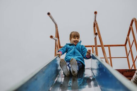 Girl child at the playground. Smiling little girl sliding at playground outdoors