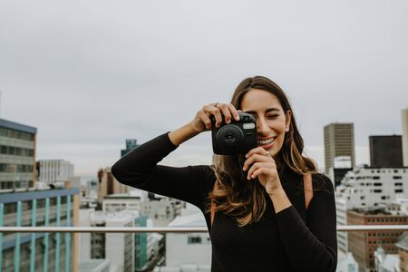 Woman standing on the terrace taking pictures with an instant camera. Female clicking photographs with a camera. 스톡 콘텐츠 - 149003731