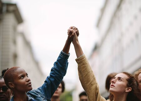 Two women activists holding hands and protesting. Protestors doing demonstration on the street holding hands.