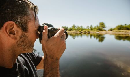 Nahaufnahme eines reifen Mannes, der mit einer DSLR-Kamera des Sees fotografiert. Männlicher Fotograf, der Bilder von einem See macht.