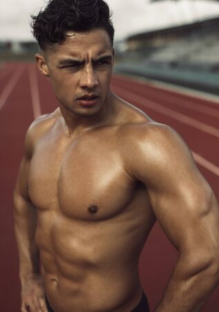 Young man with muscular body standing on a running track and looking away. Bare chested athlete relaxing after a workout standing on the track.