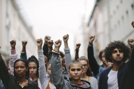 Group of protestors with their fists raised up in the air. Activists protesting on the street.