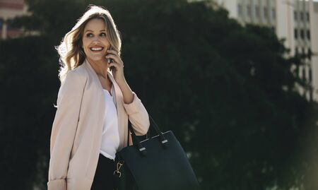 Real estate agent talking on phone while commuting. Businesswoman on phone call looking away and smiling. 스톡 콘텐츠 - 149000327
