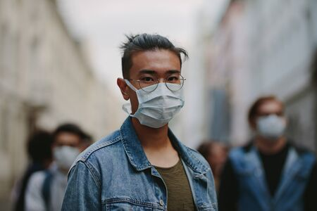 Man wearing a face mask during a global pandemic with coronavirus. Portrait of man with a crowd behind him.